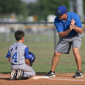 A young boy kneeling on a baseball plate on a baseball field wearing a baseball jersey with the number four on it holding a blue helmet listening to his adult male coach in grey shorts, a blue polo shirt, and a blue ball cap showing the boy how to bat with correct form.