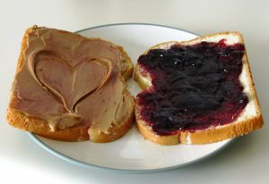 Two slices of white bread on a white plate. One slice is covered with grape jelly and the other slice is covered with peanut butter with a heart carved in the middle.