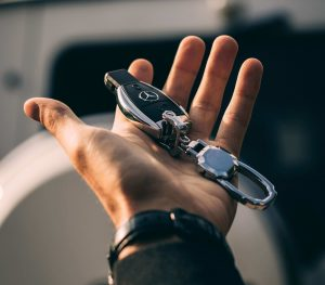 An outstretched hand holding a key with the Mercedes-Benz logo on it with an out of focus car in the background.